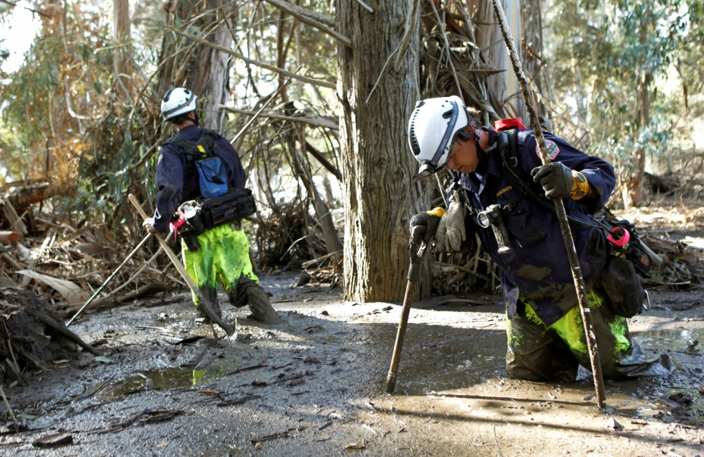 Firefighters Brandon Bennewate (R), and Billy Wren dig through mud searching for bodies after mudslides in southern California left officials searching for the missing, damaged hundreds of buildings and caked highways with sludge, in Montecito