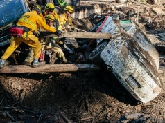 Rescue workers search in an around cars for missing persons after a mudslide in Montecito, California