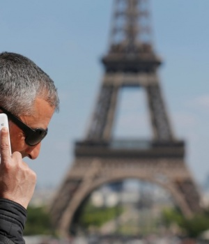 A man makes a phone call using his mobile phone at the Trocadero Square near the Eiffel Tower in Paris
