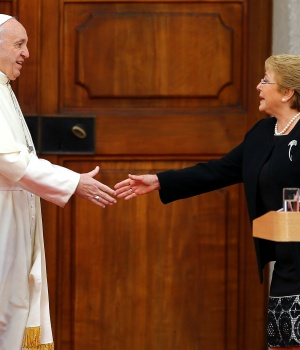 Pope Francis and Chile's President Michelle Bachelet reach out to shake hands at the La Moneda Presidential Palace in Santiago