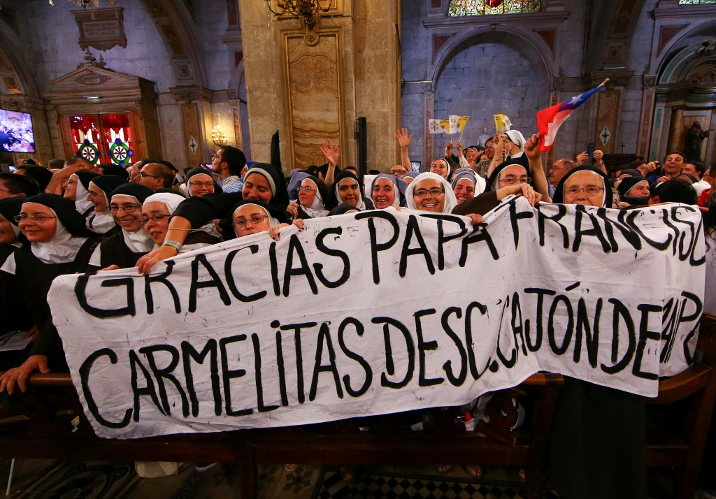 Nuns hold a banner as Pope Francis arrives to visit the Cathedral in Santiago