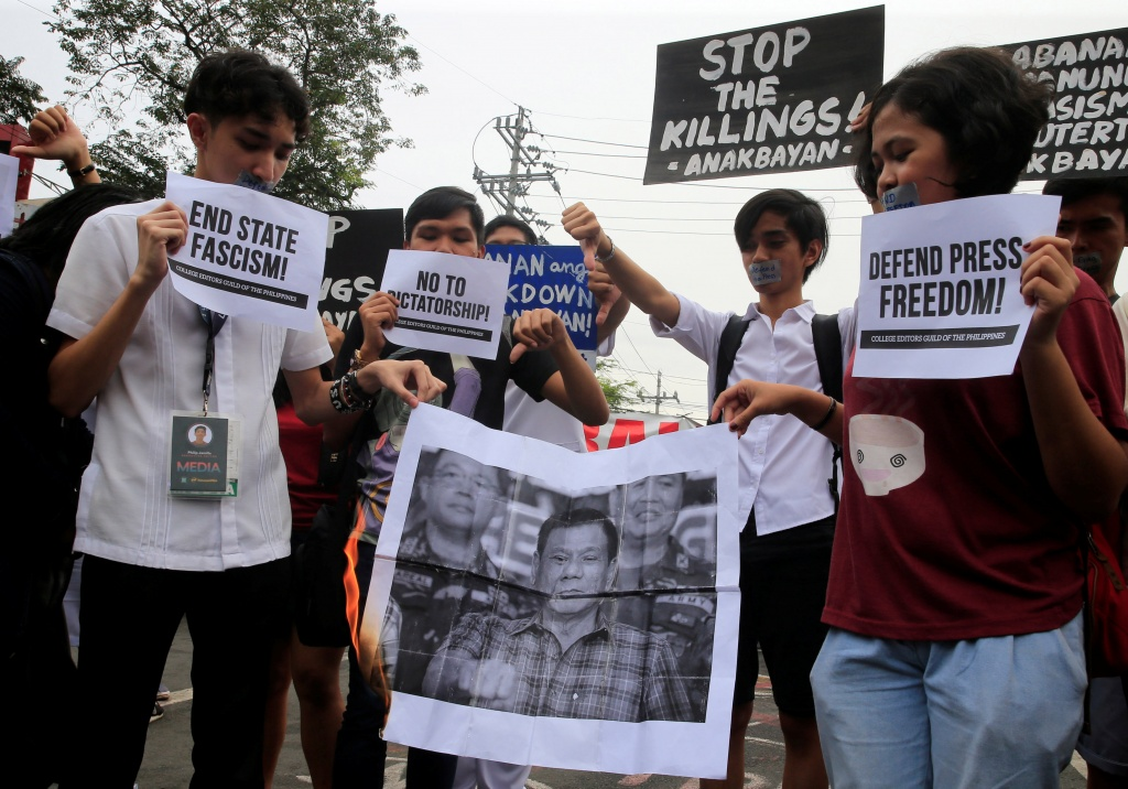 Members of the College Editors Guild of the Philippines hold placards while burning a picture of President Rodrigo Duterte during a protest outside the presidential palace in Metro Manila