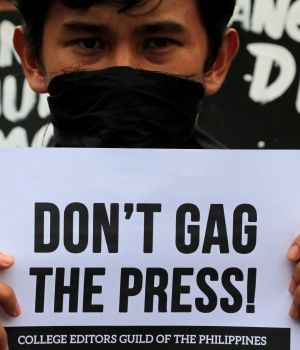 A member of the College Editors Guild of the Philippines displays a placard during a protest outside the presidential palace in Metro Manila