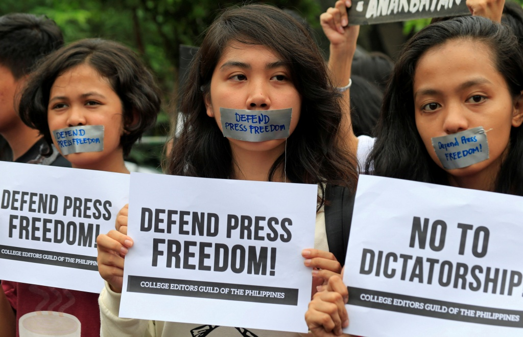 Members of the College Editors Guild of the Philippines hold placards during a protest outside the presidential palace in Metro Manila