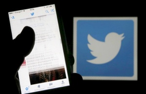 A man reads tweets on his phone in front of a displayed Twitter logo in Bordeaux, southwestern France