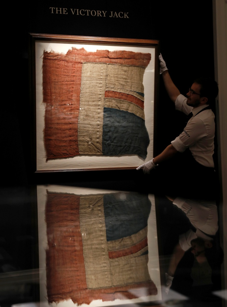 A member of Sotheby's staff poses for a photograph with a large fragment of Lord Nelson's union flag