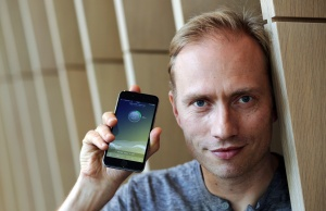 Co-founder of Sweatcoin Oleg Fomenko poses with the app open on a phone at his London office