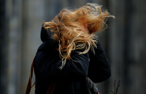 The hair of a woman is whirled during heavy storms in Cologne