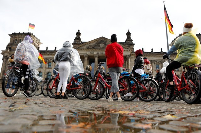 People in rainwear stand in front of the Reichstag in Berlin