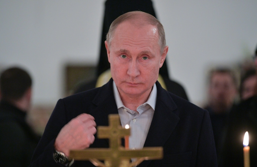 Russian President Vladimir Putin crosses himself as he attends a service for Orthodox Epiphany celebrations at the Nilov monastery on Stolobny Island on lake Seliger in the Tver Region