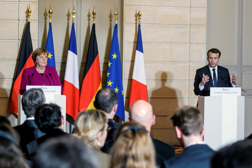 French President Emmanuel Macron and German Chancellor Angela Merkel attend a joint news conference before a meeting at the Elysee Palace in Paris