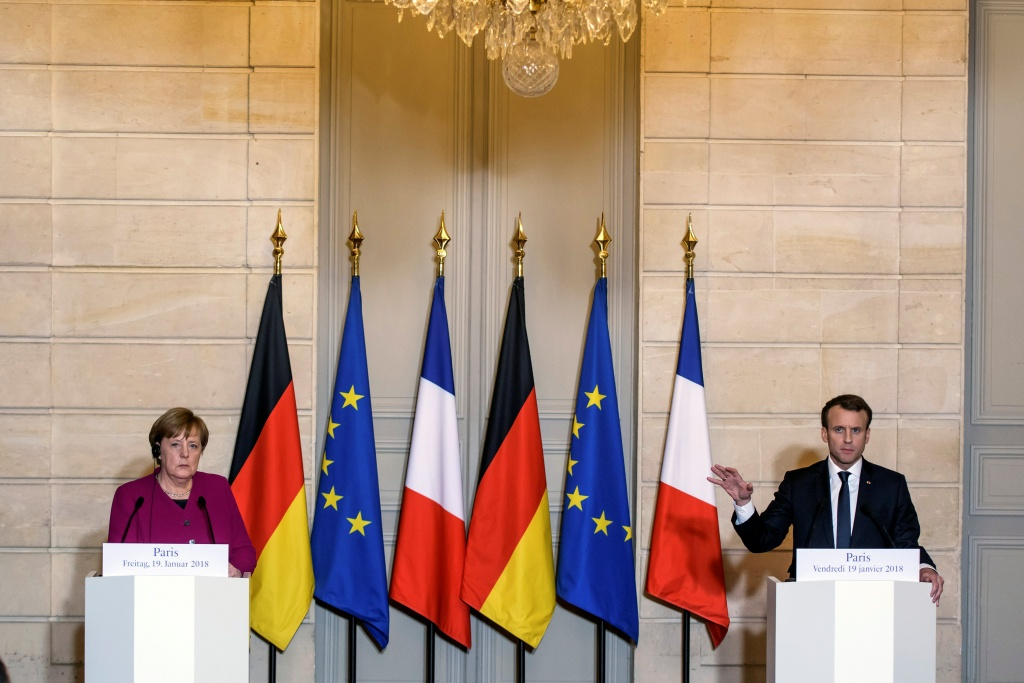 French President Emmanuel Macron and German Chancellor Angela Merkel attend a joint news conference before a meeting at Elysee Palace in Paris