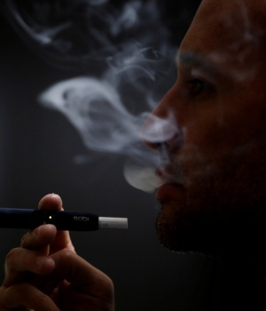 A man poses for a photograph while using a Philip Morris iQOS smoking device in Bogota