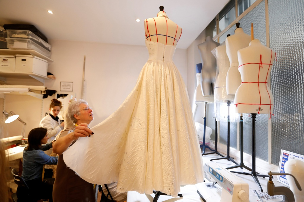 Madame Jacqueline, head seamstress, works on a wedding dress at the Maison Julien Fournie workshop in Paris