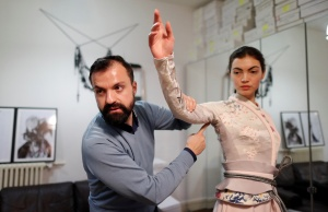 French designer Julien Fournie adjusts a creation on model Daphne during a fitting at his workshop ahead of his Spring-Summer 2018 Haute Couture fashion show presentation in Paris