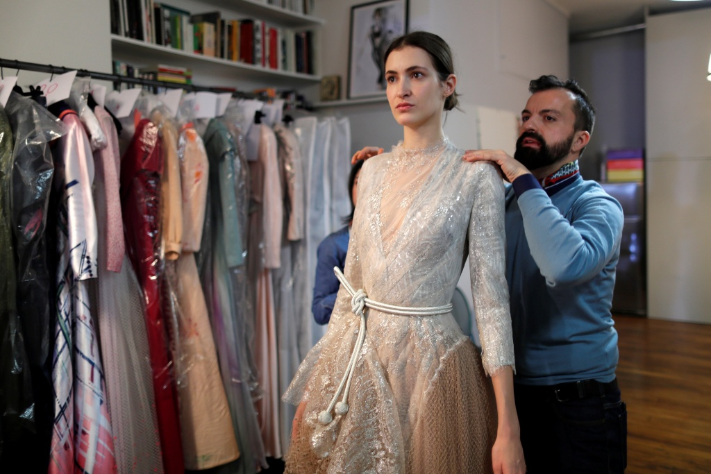French designer Julien Fournie adjusts a creation on model Greta during a fitting at his workshop ahead of his Spring-Summer 2018 Haute Couture fashion show presentation in Paris