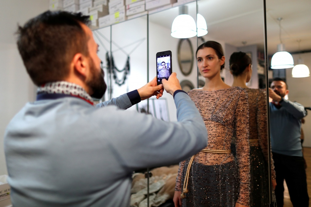French designer Julien Fournie takes pictures of model Greta during a fitting at his workshop ahead of his Spring-Summer 2018 Haute Couture fashion show presentation in Paris