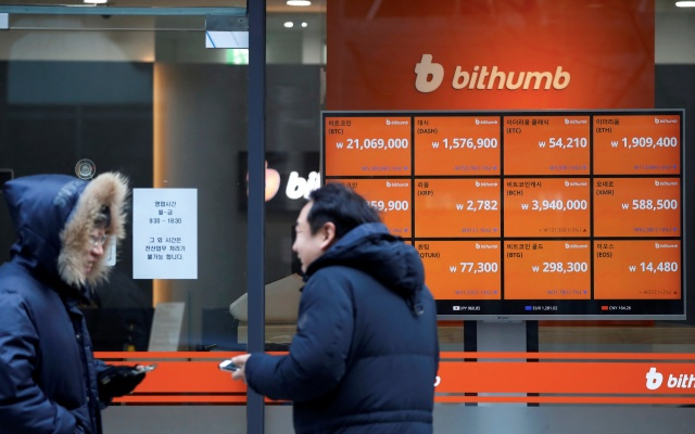 Men talk in front of an electric board showing exchange rates of various cryptocurrencies at Bithumb cryptocurrencies exchange in Seoul