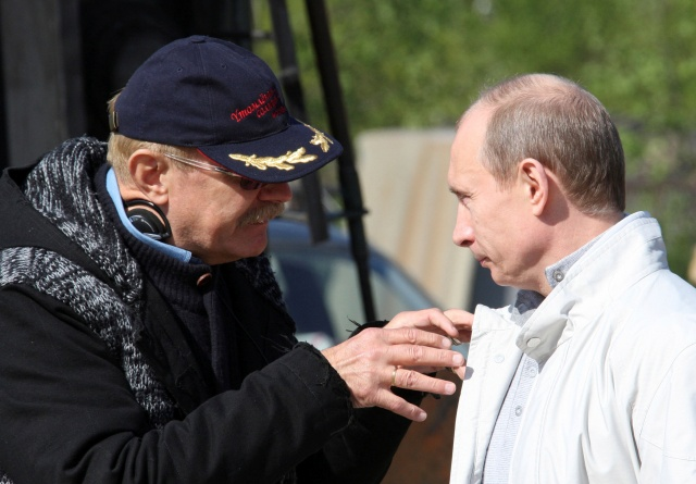Putin listens to explanations from film director Nikita Mikhalkov at a shooting area of a movie outside St.Petersburg