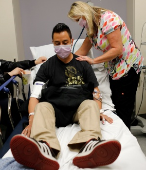 Emergency room nurse Christine Bauer treats Joshua Lagade of Vista, California, for the flu as his girlfriend Mayra Mora looks on in the emergency room at Palomar Medical Center in Escondido, California,