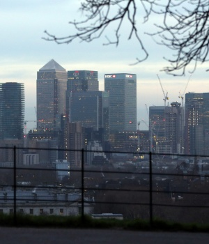 A man takes a photograph of the Canary Wharf financial district from Greenwich Park in London