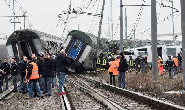 Rescue workers and police officers stand near derailed trains in Pioltello, on the outskirts of Milan