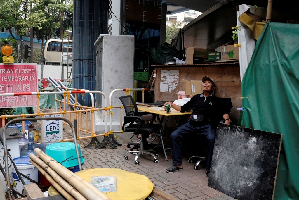 Cheung Muk-gun, 72, drinks a can of beer outside his makeshift home under a footbridge in Hong Kong