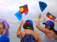 Passengers aboard a ferry wave the Australian Aboriginal flag as they participate in celebrations for Australia Day, which marks the arrival of Britain's First Fleet in 1788, on Sydney Harbour
