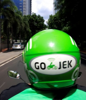 A Go-Jek driver rides a motorcycle on a street in Jakarta, Indonesia