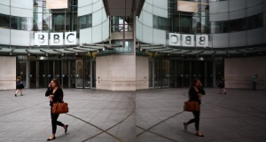 A woman is reflected as she passes the BBC's Broadcasting House in London