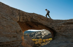 A man walks over a natural bridge at Butler Wash in Bears Ears National Monument near Blanding