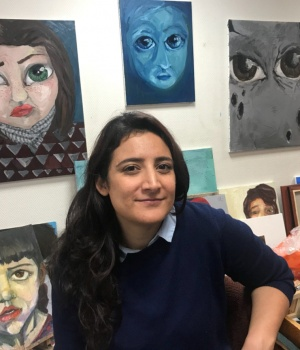 Syrian artist Lina Aljijakli poses with her paintings in the Atelier for Artists in Exile in Paris