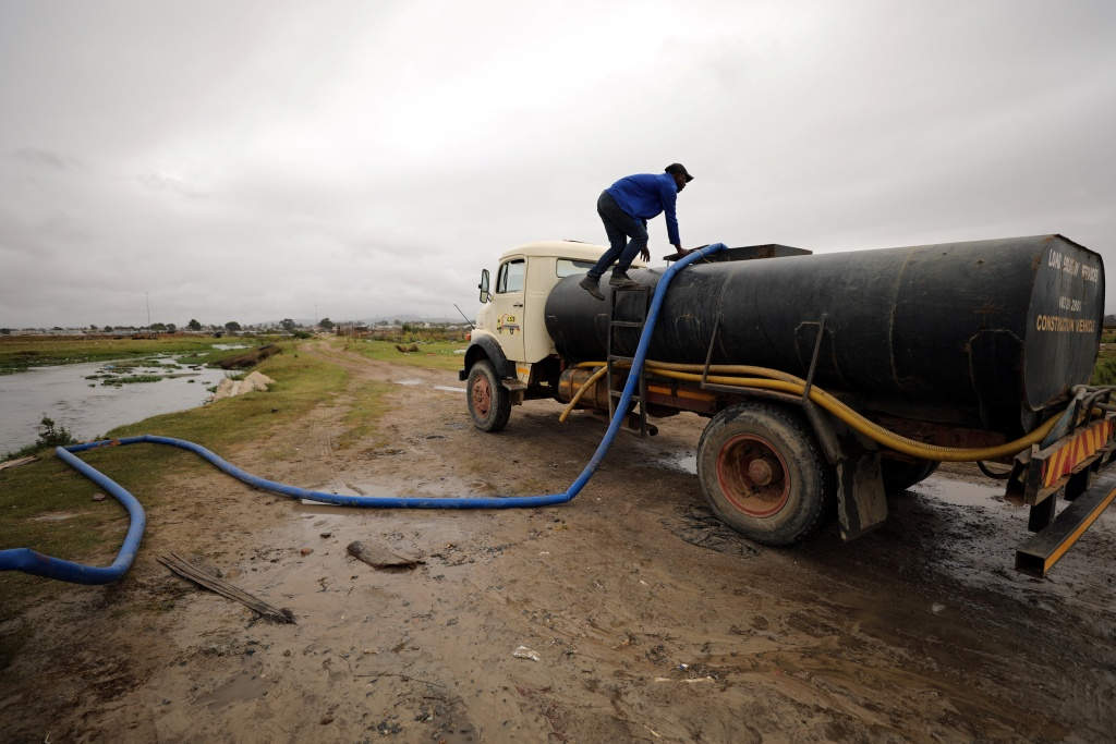 A man fills up a tanker with water from a polluted river as the city's water crisis mounts near Cape Town