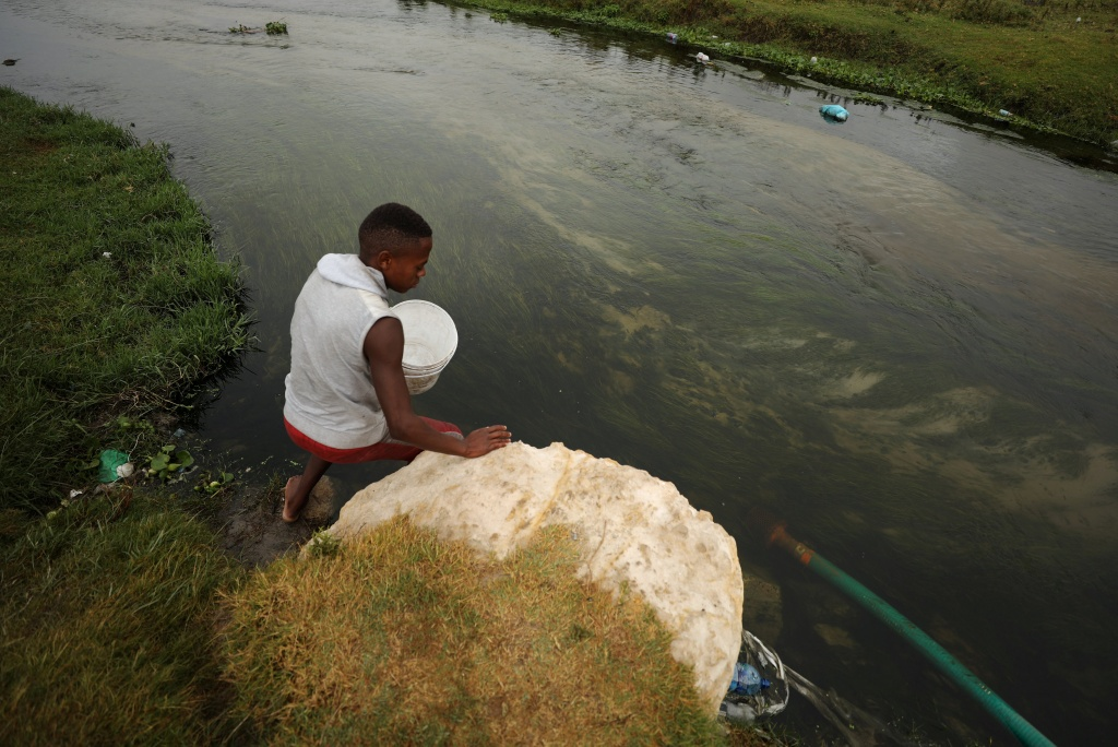 A man fills up a containers with water from a polluted river as the city's water crisis mounts near Cape Town
