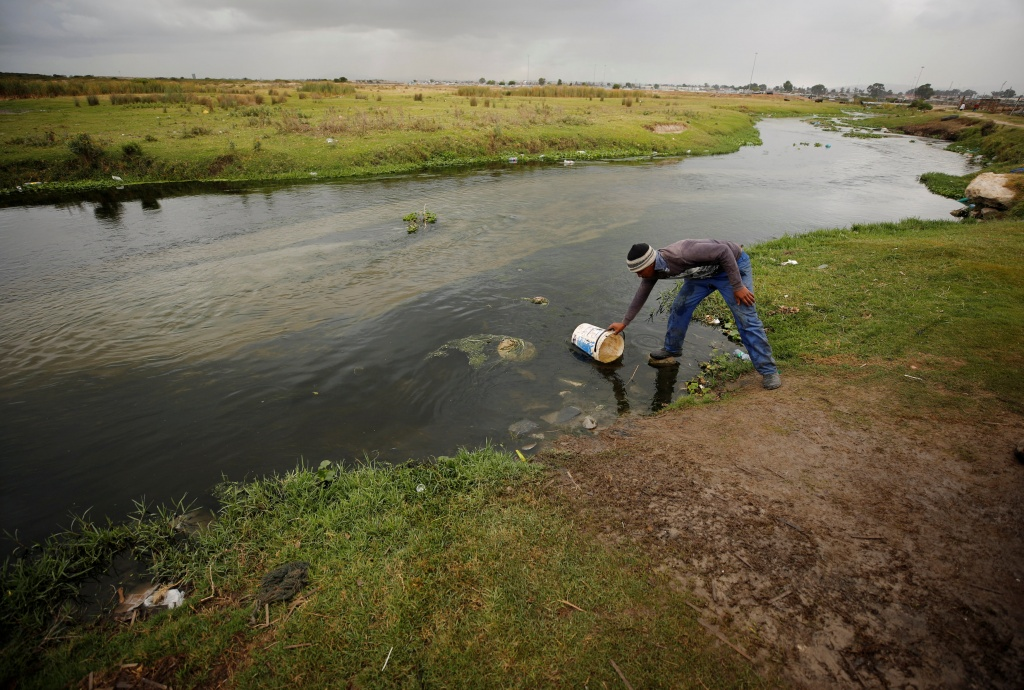 Residents fill containers with water from a polluted river in Cape Town