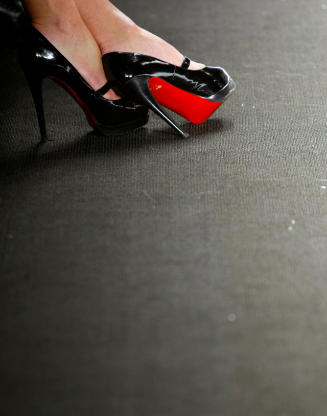A woman wearing a pair of Christian Louboutin shoes sits in the front row at the Project Runway Fall 2010 collection during New York Fashion Week