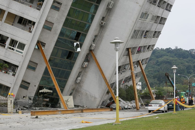 Rescue workers are stand next to a damaged building after an earthquake hit Hualien