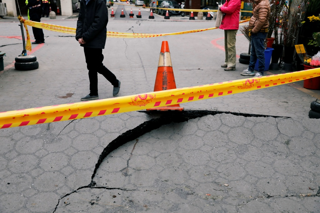 A passerby walks behind cracks on a street after an earthquake hit Hualien