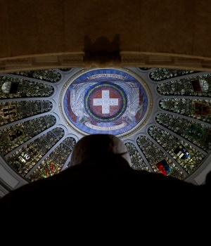 A Swiss flag is depicted on the ceiling above the statue of the Three Confederates in the Swiss Parliament Building (Bundeshaus) in Bern