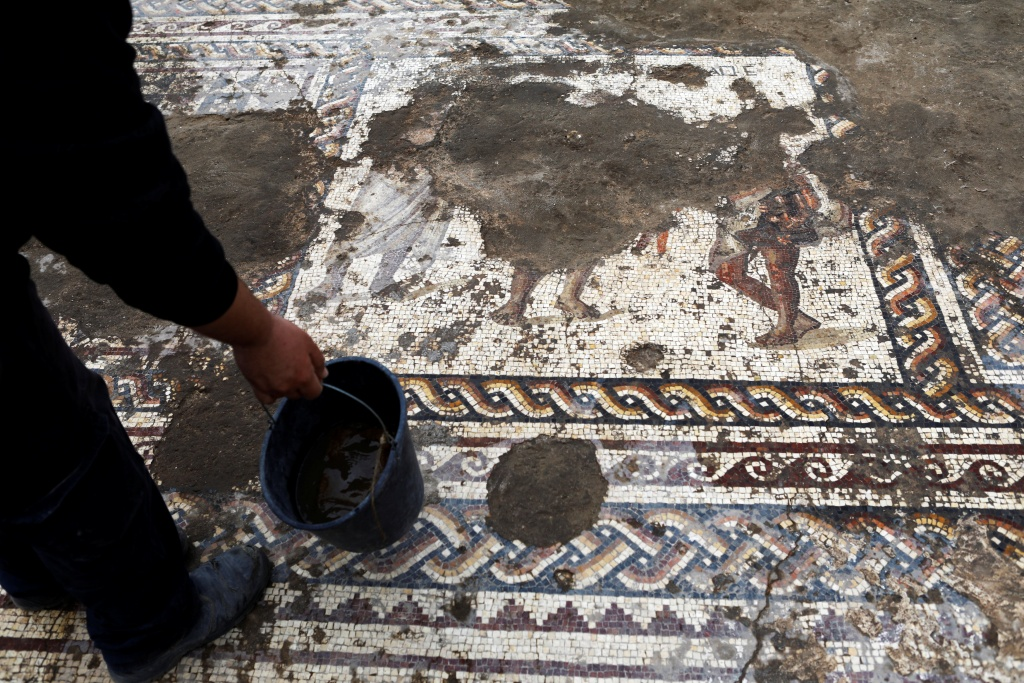An Israel Antiquities Authority worker holds a bucket while cleaning a mosaic floor decorated with figures, which archaeologists say is 1,800 years old and was unearthed during an excavation in Caesarea