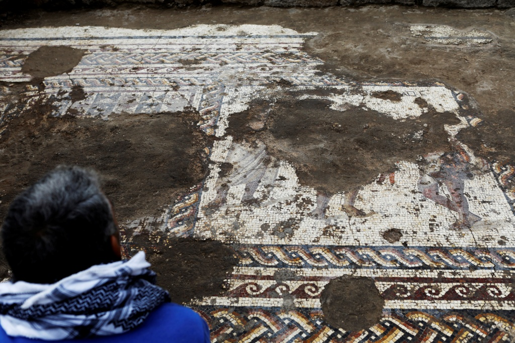 An Israel Antiquities Authority worker looks at a mosaic floor decorated with figures, which archaeologists say is 1,800 years old and was unearthed during an excavation in Caesarea