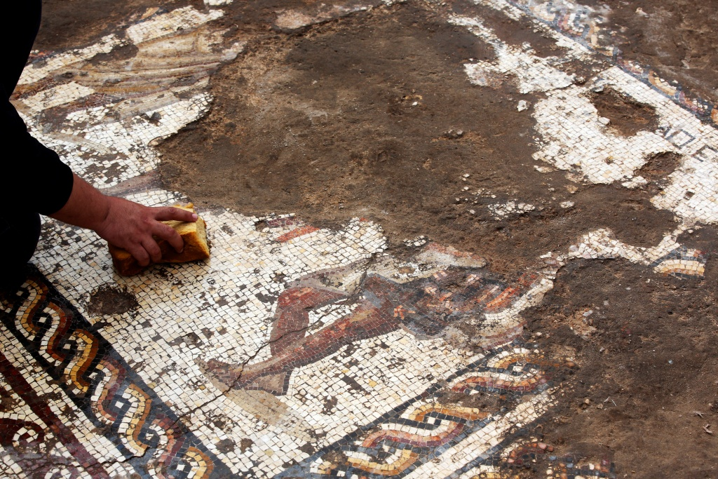 An Israel Antiquities Authority worker cleans a mosaic floor decorated with a figure, which archaeologists say is 1,800 years old and was unearthed during an excavation in Caesarea