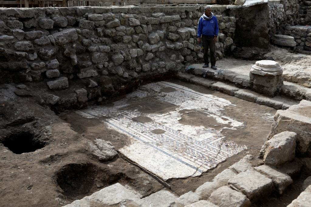 An Israel Antiquities Authority worker stands next to a mosaic floor which archaeologists say is 1,800 years old and was unearthed during an excavation in Caesarea