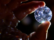 An assistant holds a 102.34 carat white diamond at Sotheby's auction house in London
