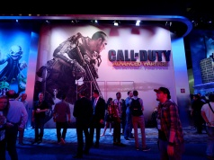 "Attendees walk pass a giant billboard promoting the new multiplayer action game ""Call of Duty: Advanced Warfare"" in Los Angeles"
