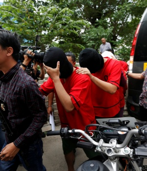 "A plainclothes policeman holds a rifle as he escorts suspects during a police investigation into a men's club after a weekend raid on what authorities described as a ""gay spa"" in Jakarta, Indonesia"