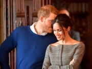 Britain's Prince Harry whispers to Meghan Markle as they watch a performance by a Welsh choir in the banqueting hall during a visit to Cardiff Castle in Cardiff