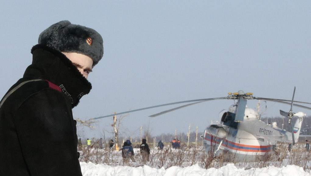 A Russian serviceman looks back as he stands guard during a search operation near the crash site of the AN-148 airplane in Moscow Region