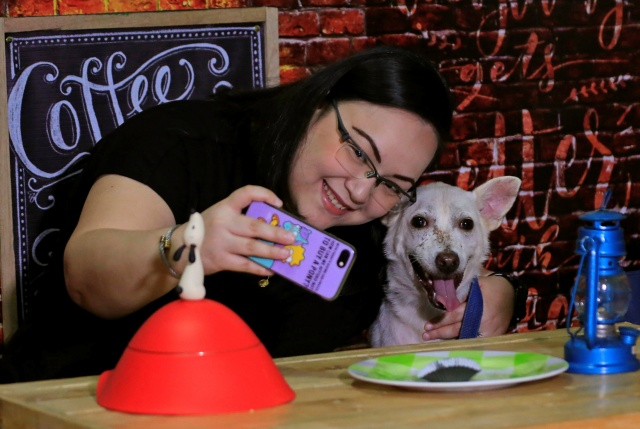 A pet lover takes a selfie with a shelter dog during a