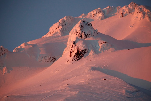 At sunset, climbers and rescue personnel descend Mount Hood